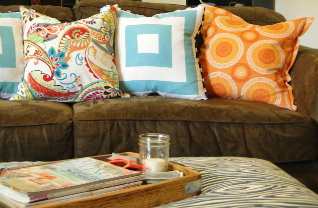 Light and bright pillows help disguise a dark couch