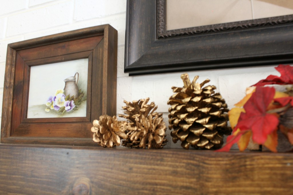 gold-pine-cones-and-small-painting-on-mantel