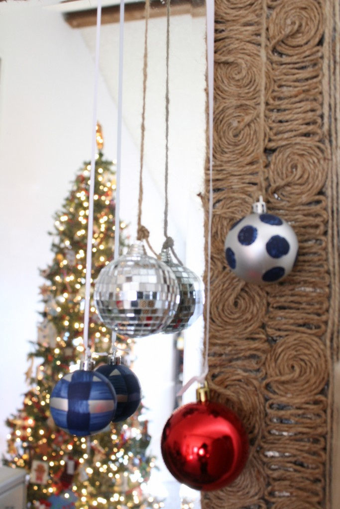ornaments hung on a mirror for a festive touch
