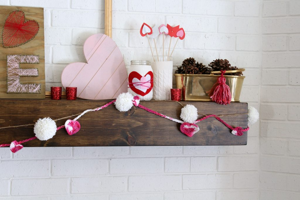 Hearts, tassels, and pom poms make this mantel cute!