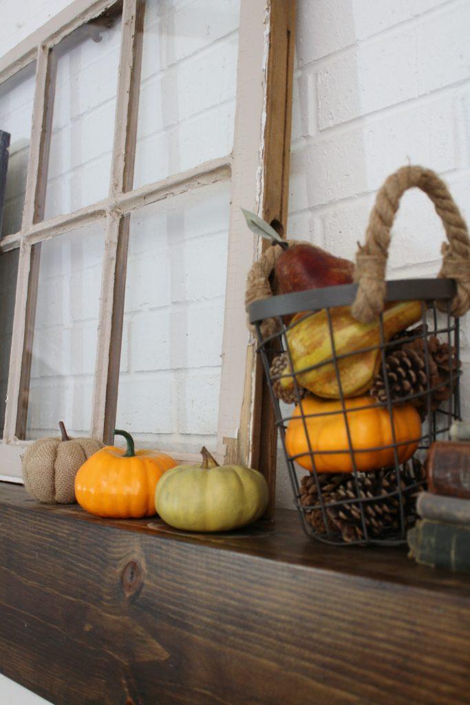 Fall mantel pumpkins and pine cones