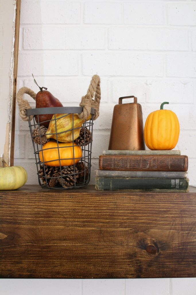 Pumpkins and copper cowbell for fall mantel