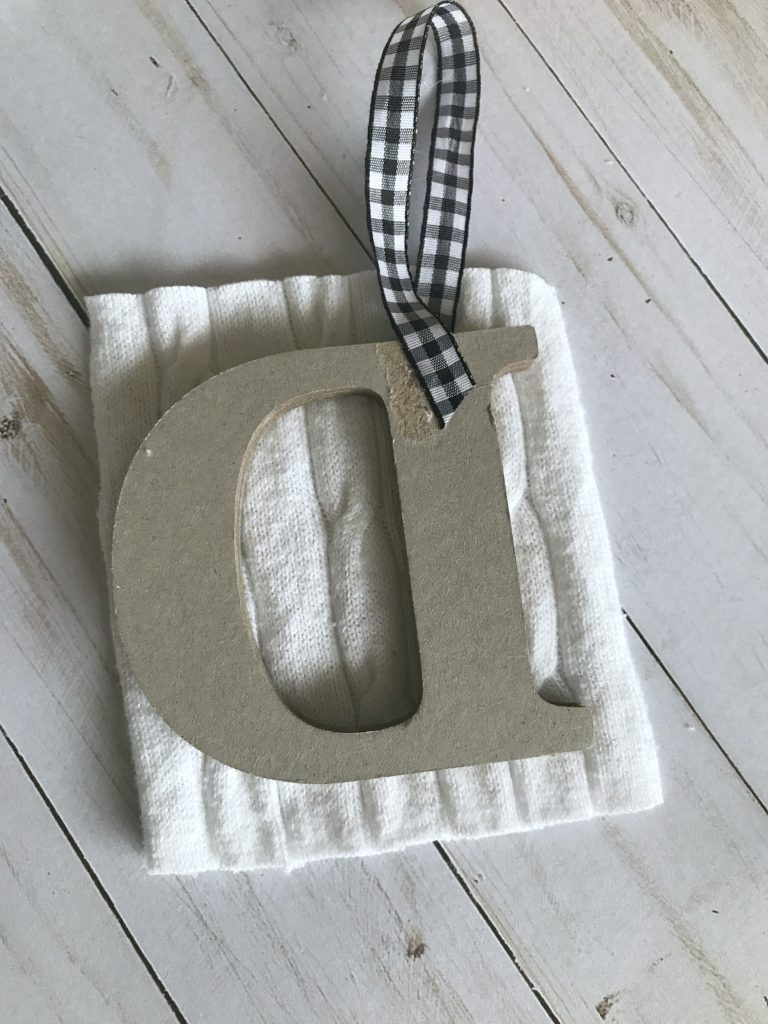Cut a square of sweater or other fabric a little large than your letter.