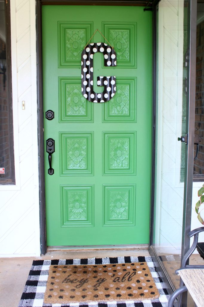 Green painted front door with black and white accessories