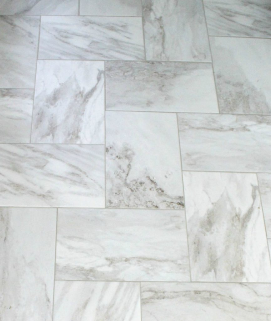 Close up of marble look tile in straight herringbone pattern with light gray grout