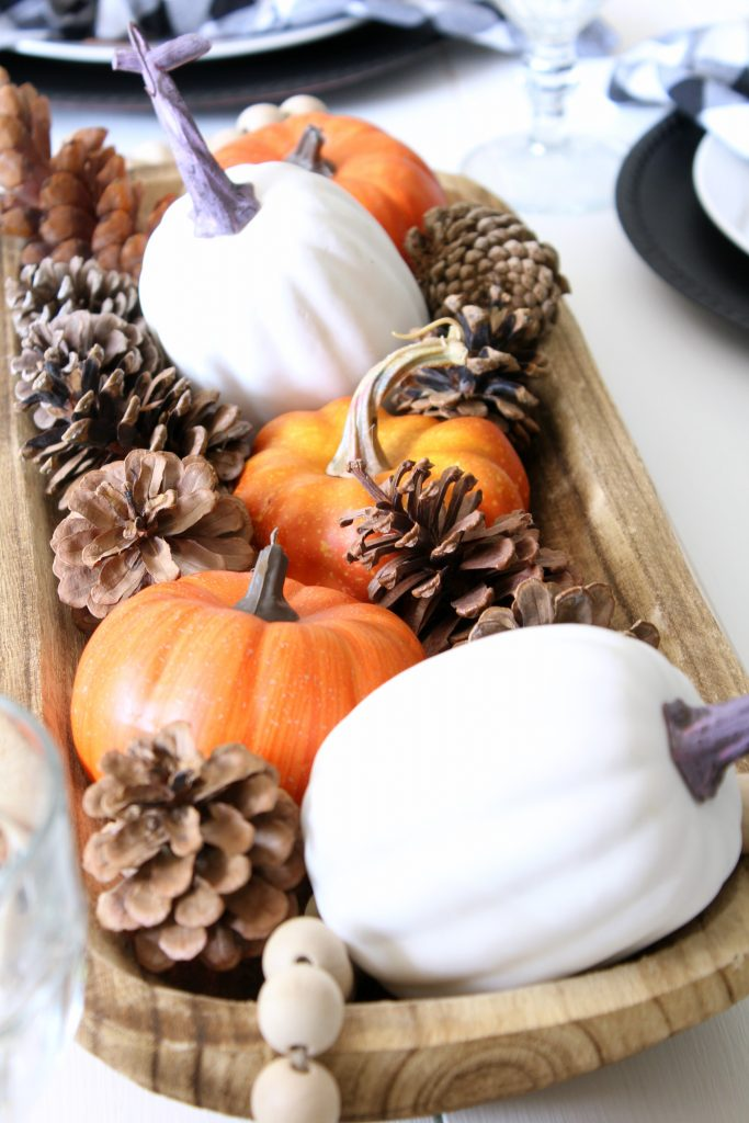 Faux pumpkins mixed with pine cones for fall centerpiece