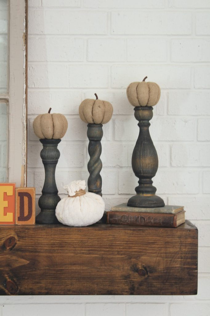 Pumpkins atop candlesticks fall mantel decor
