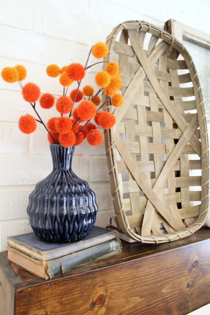 Orange poms and tobacco basket fall mantel decor