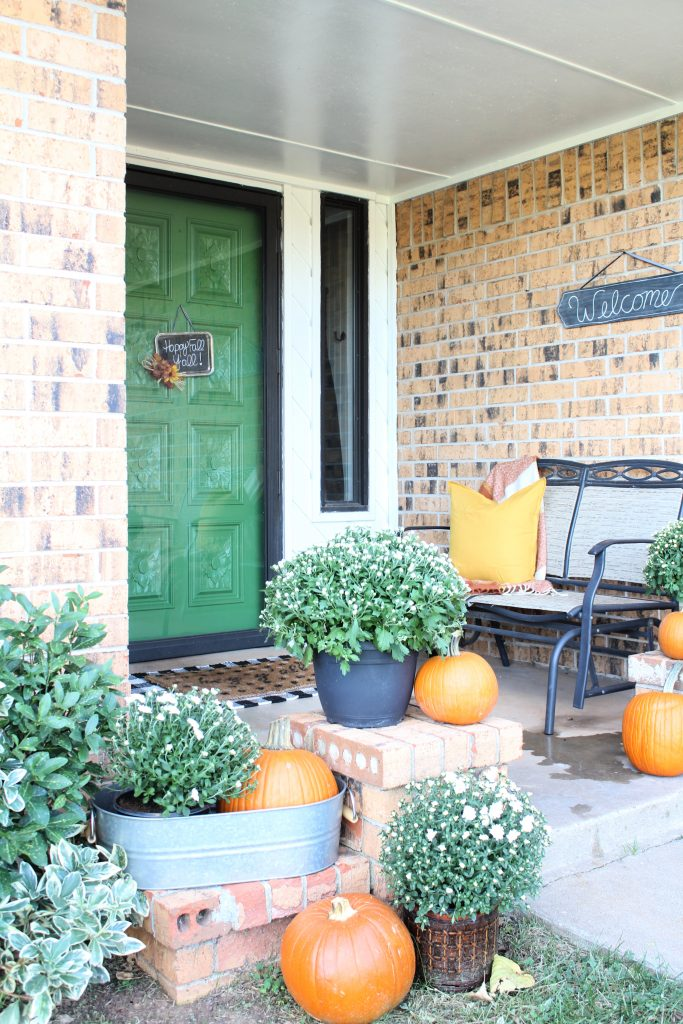 Fall front porch with orange pumpkins and white mums